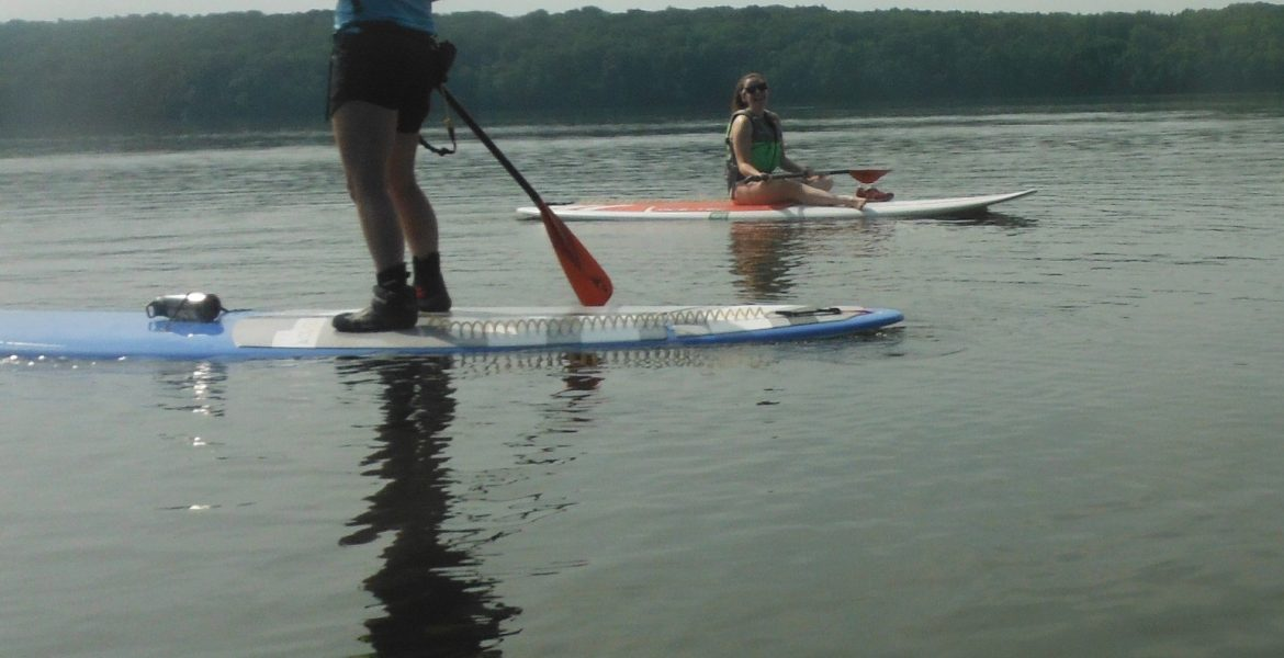 A woman on a stand up paddle board, another sits on one in the background
